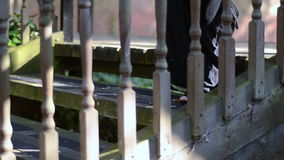 Close up of a woman`s legs walking along a boardwalk and down some stairs. stock footage