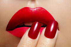 Close-up of woman`s lips with fashion red make-up and manicure. Beautiful female full lips with perfect makeup Royalty Free Stock Images