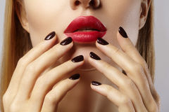 Close-up of woman`s lips with fashion red make-up and manicure. Beautiful female full lips with perfect makeup Stock Photo