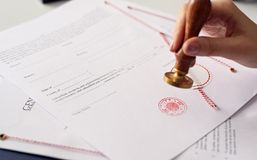 Close up on woman's notary public hand ink stamping the document Stock Photography