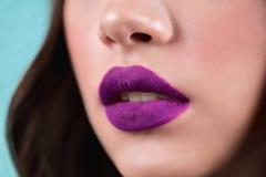 Close up of the woman`s open lips. Purple lipstick, lip gloss, cosmetics. stock photo