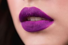 Close up of the woman`s open lips. Purple lipstick, lip gloss, cosmetics. stock images