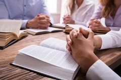 Woman`s Praying Hand On Bible. Close-up Of A Woman`s Praying Hand On Bible Over Wooden Desk royalty free stock photos