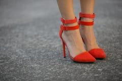 Woman`s red leather heels on asphalt. Close up of woman`s red sued and leather heels standing on asphalt Stock Image