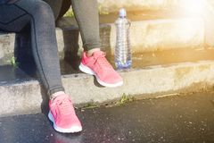 Close up of woman´s sports shoes. Young woman have a rest on stairs. Healthy lifestyle. Fitness sport. Cardio training. Smart phone and bottle of fresh water Royalty Free Stock Image
