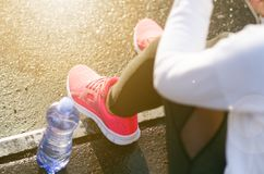 Close up of woman´s sports shoes. Young woman have a rest on stairs. Healthy lifestyle. Fitness sport. Cardio training. Smart phone and bottle of fresh water Stock Photo