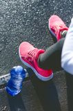 Close up of woman´s sports shoes. Young woman have a rest on stairs. Healthy lifestyle. Fitness sport. Cardio training. Smart phone and bottle of fresh stock image
