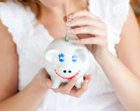 Close-up of a woman saving money in a piggy-bank. At home Stock Photo