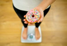 Close up of woman on scale holding delicious donut in obesity and unhealthy food concept royalty free stock images