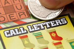 Close up woman scratching lottery ticket. Royalty Free Stock Images