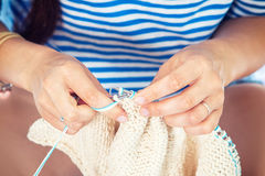 Close up woman sews a button. Close-up Young brunette woman r sews a button with a needle on a pink knitted sweater Stock Photos