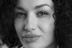 Close up of a woman with sexy look in black and white. Black and white close up portrait of a confident friendly woman with afro hair and sexy look Royalty Free Stock Images