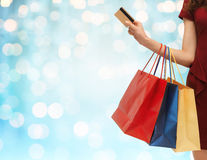 Close up of woman with shopping bags and bank card. People, sale and consumerism concept - close up of woman with shopping bags and bank or credit card over blue Stock Images