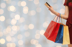 Close up of woman with shopping bags and bank card. People, sale and consumerism concept - close up of woman with shopping bags and bank or credit card over Stock Photography
