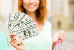Close up of woman with shopping bags and money Royalty Free Stock Images