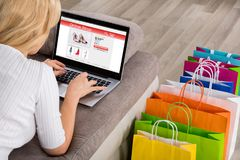 Close-up Of Woman Shopping Online Using Laptop. With Colorful Shopping Bags On Floor Stock Photos
