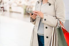 Close up woman shopping at store. Let`s go shopping!. Close up woman shopping at store and using smartphone. Let`s go shopping Stock Photos