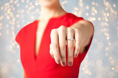 Close up of woman showing hand and engagement ring. Holidays, jewelry and people concept - close up of woman showing engagement ring on her hand over lights royalty free stock photo