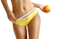 Close up of a woman showing hips with a fruit in her hand Royalty Free Stock Images