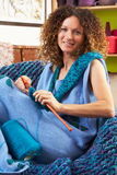 Close Up Of Woman Sitting In Chair Knitting. Smiling Stock Photos