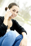 Close up of woman sitting with legs bent on phone Royalty Free Stock Photography