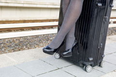 Close-up of woman sitting on suitcase at train station Stock Images