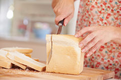 Close Up Of Woman Slicing Loaf Of Bread In Kitchen Royalty Free Stock Photos