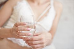 Close-up woman with slim body holding a glass of water. royalty free stock images
