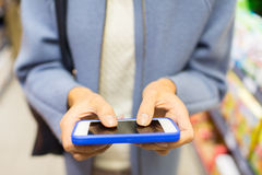 Close up of woman with smartphone in market Royalty Free Stock Image