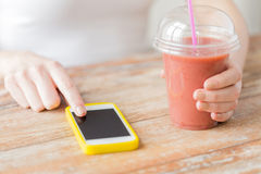 Close up of woman with smartphone and smoothie Royalty Free Stock Photo