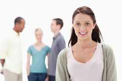 Close-up of a woman smiling with friends. Close-up of a women smiling with friends chatting in background Royalty Free Stock Images