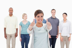 Close-up of a woman smiling giving the thumbs-up with people beh Royalty Free Stock Photo