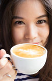 Close up of woman smiling and holding cup of  cappuccino coffee Stock Photography