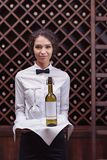 Close-up woman sommelier standing with bottle of wine and glass on tray. In cellar stock images