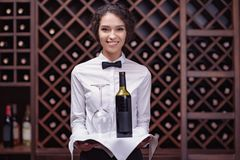 Close-up woman sommelier standing with bottle of wine and glass on tray. In cellar stock image