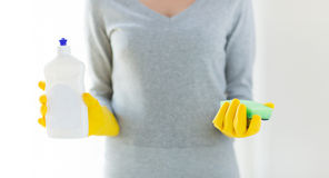 Close up of woman with sponge and cleanser. People, housework, washing-up and housekeeping concept - close up of woman holding sponge and cleanser bottle at home Stock Image