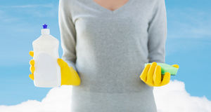 Close up of woman with sponge and cleanser. People, housework, washing-up and housekeeping concept - close up of woman holding sponge and cleanser bottle over Royalty Free Stock Photography