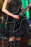 Close-up of a woman on stage playing on electro guitar. The girl rockstar in a black dress.  Royalty Free Stock Photos