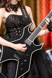 Close-up of a woman on stage playing on electro guitar. The girl rockstar in a black dress.  Stock Photo
