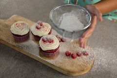 Woman staining flour on cupcakes Stock Photo