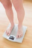 Close up of woman standing on weighing scale. In a fitness studio stock photography