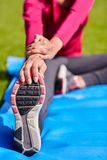 Close up of woman stretching leg on mat outdoors Stock Photo