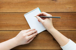Close up of woman or student writing to notepad Stock Image