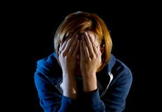 Close up woman suffering depression and stress crying alone. Young woman suffering depression and stress sitting alone in pain and grief covering face with hands Royalty Free Stock Photography