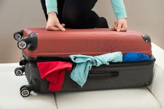 Close-up of woman with suitcase. Close-up Of Woman Trying To Close Suitcase With Excess Of Clothes Stock Photography