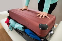 Close-up of woman with suitcase. Close-up Of Woman Trying To Close Suitcase With Excess Of Clothes Stock Images