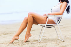 Close up of woman sunbathing in lounge on beach Stock Image
