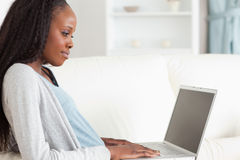 Close up of woman surfing the internet. Close up of young woman surfing the internet on the couch Stock Images