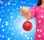 Close up of woman in sweater with christmas ball Stock Images