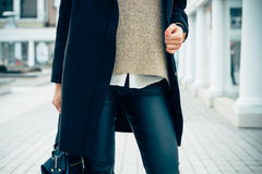 Close-up of a woman in a sweater, coat, black pants. Details of women's clothing. Close-up of a woman in a sweater, coat, black pants. In her hand female bag Royalty Free Stock Images